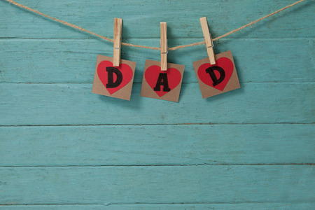 Text dad in heart shapes hanging on green wooden wall
