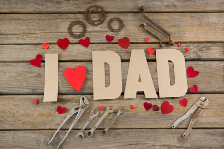 High angle view of dad text with hand tools and heart shapes decoration on table