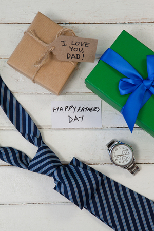 Overhead view of happy fathers day text with gifts boxes on wooden table