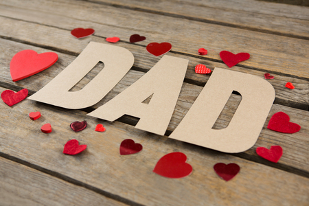 High angle view of dad text with red heart shapes on wooden table