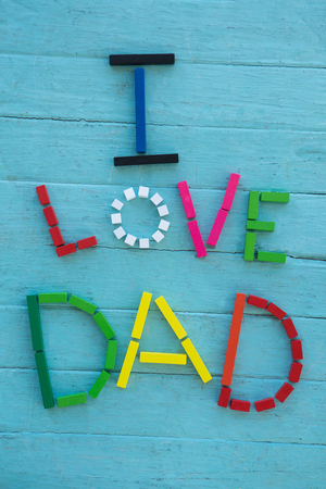 Overhead view of multi colored i love dad text on blue table Stock Photo
