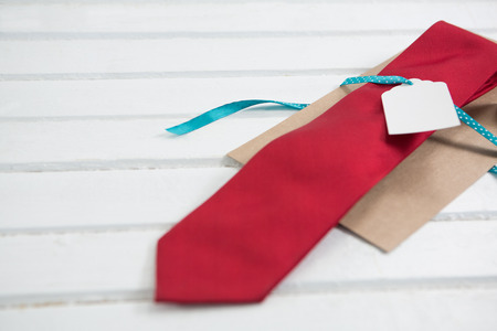 High angle view of necktie with price tag on wooden table