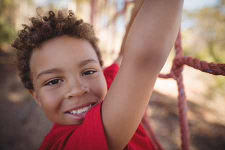 Portrait of happy boy climbing a net during obstacle course in boot camp Stock Photo