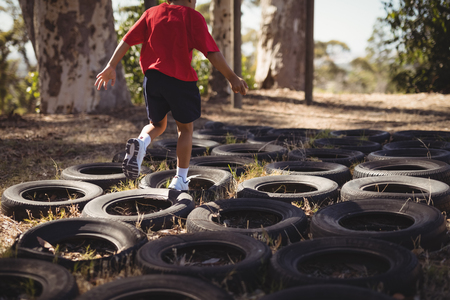 Boy running over tyres during obstacle course in boot camp Standard-Bild