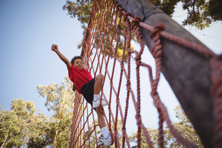 Happy boy cheering while climbing a net during obstacle course in boot camp