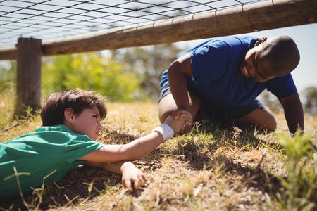 Boy helping his friend during obstacle course in boot camp