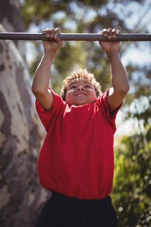 Boy performing pull-ups on bar during obstacle course in boot camp