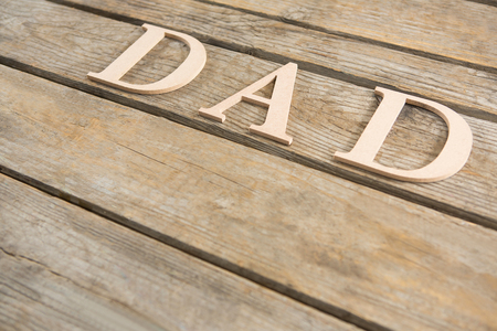 High angle view of dad text on wooden table
