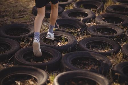 장애물 코스 동안 타이어를 실행하는 소녀의 낮은 섹션 스톡 콘텐츠