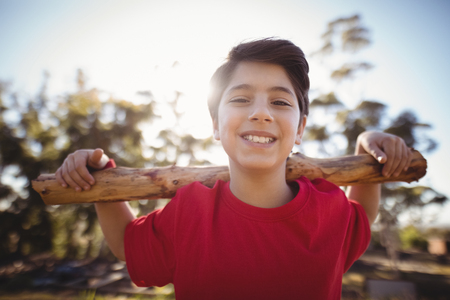Portrait happy boy exercising with log during obstacle course in boot camp
