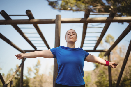 Beautiful woman exercising during obstacle course in boot camp Stock Photo
