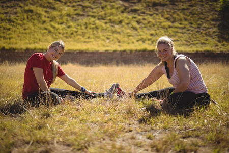 Happy friends performing stretching exercise during obstacle course in boot camp Stock Photo