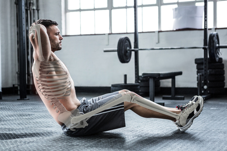 Digital composite of highlighted bones of exercising man at gym Stock Photo