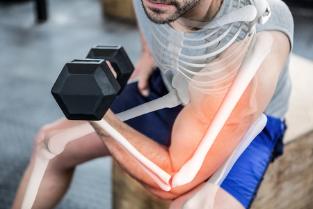 Digital composite of highlighted arm of strong man lifting weights at gym