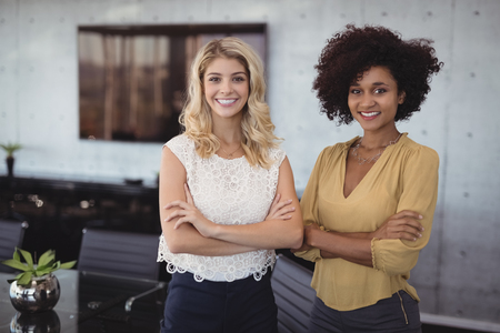 Portrait of smiling female colleagues standing in meeting room at office Stock Photo