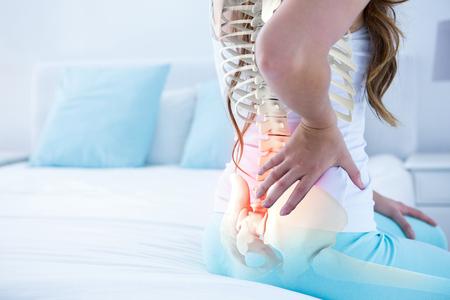 Composito digitale di colonna vertebrale evidenziata di donna con mal di schiena a casa Archivio Fotografico - 79269533