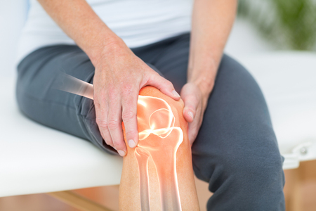Digitally composite image of man suffering with knee cramp Stockfoto