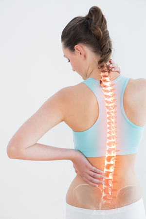 Rear view of woman suffering from pain against white background Stock Photo
