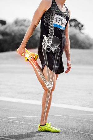 Digital composite of highlighted bones of athlete man stretching on race track Foto de archivo