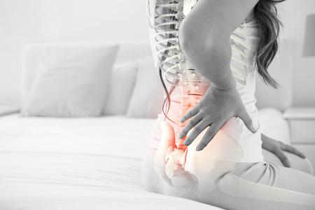 腰痛を自宅で女性の強調表示された背骨のデジタル合成 写真素材
