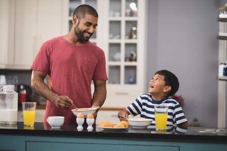 niños desayunando: Happy young father with his son having breakfast in kitchen at home