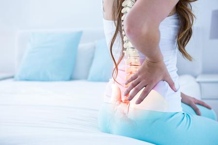 Composite numérique de la colonne vertébrale en surbrillance de la femme avec maux de dos à la maison Banque d'images - 79269983
