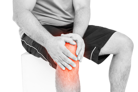 middle joint: Mid section of man suffering with knee pain against white background Stock Photo
