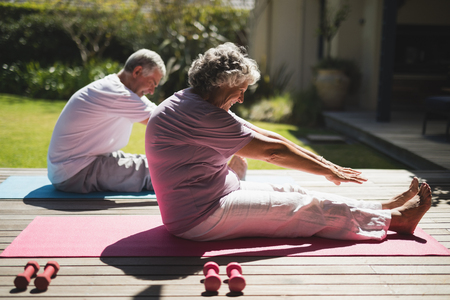 Senior couple exercising together while sitting on mat at porch Stock Photo