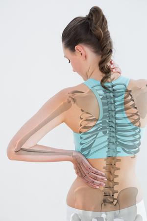 Achtermening van wijfje die aan spierpijn lijden tegen witte achtergrond