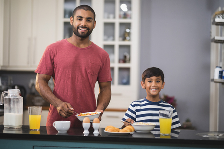 niños desayunando: Portrait of happy young father and his son having breakfast in kitchen at home