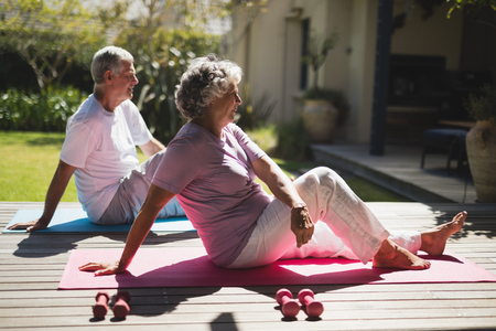 Side view of senior couple exercising together while sitting on mat at porch Stock Photo - 79271803