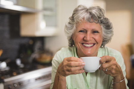 Portrait of happy senior woman holding cup at home