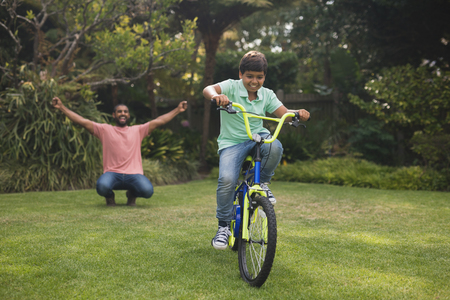 Father cheering for boy riding bicycle at park