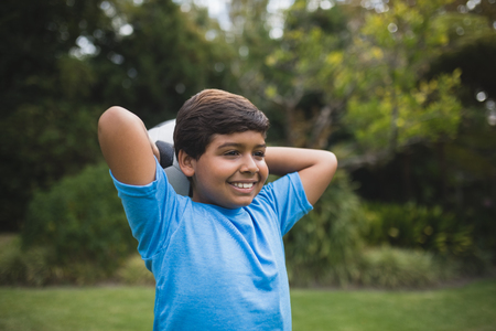 arms behind head: Smiling boy holding soccer ball behind head at park