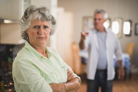 Retrato de mujer senior cara seria con hombre enojado en segundo plano en casa Foto de archivo - 79278198