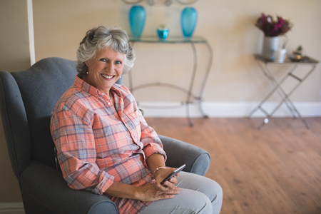 Portrait of smiling senior woman holding mobile phone while sitting on armchair at home Stock Photo