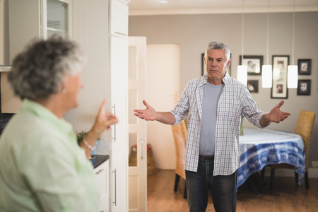 Angry senior man looking at female partner in living room