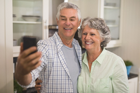 Cheerful senior couple taking selfie in kitchen at home