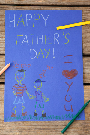 Close-up of paintings and happy fathers day message on paper