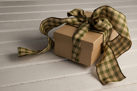 Close-up of tied gift box on wooden plank