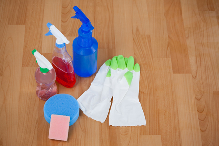 Close-up of glove with cleaning equipment on wooden floor Imagens