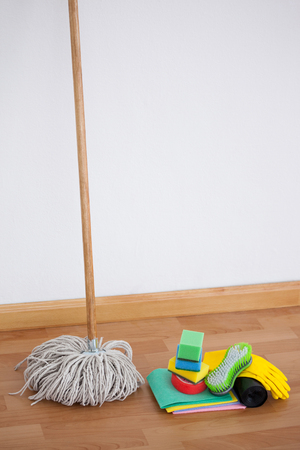 Mop and cleaning equipment on wooden floor against wall Imagens - 79309223