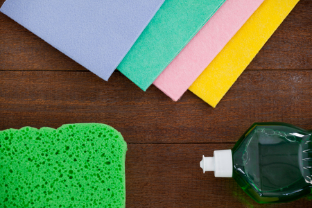 scrubber: Detergent spray bottle and various cleaning pad on wooden floor