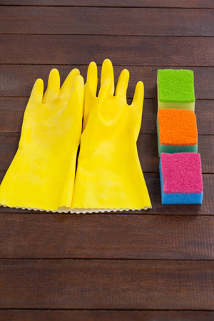 Close-up of glove and scrubber arranged on wooden floor Imagens