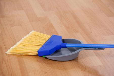 closeup of sweeping broom with dustpan on wooden floor photo