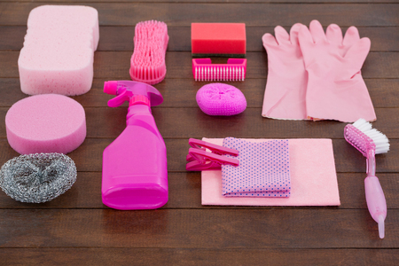 Close-up of pink color cleaning equipment arranged on wooden floor