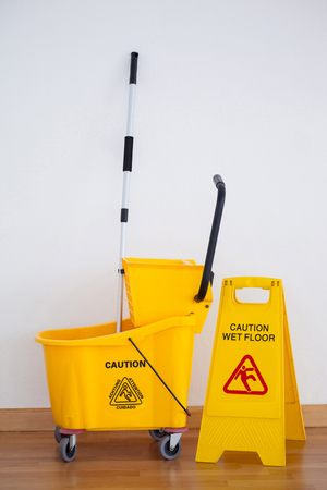 Yellow sign board with mop bucket on wooden floor against wall