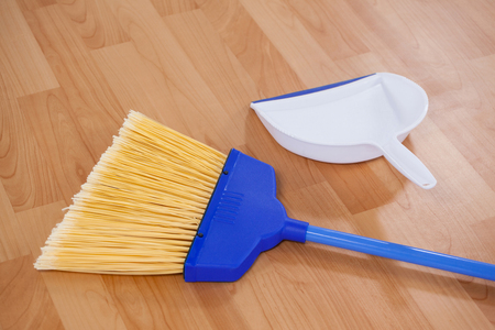 closeup of sweeping broom and dustpan on wooden floor photo