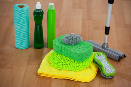 Close-up of various housekeeping supplies on wooden floor