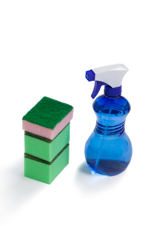 Cleaning spray bottle and stack of scrubber on white background Imagens